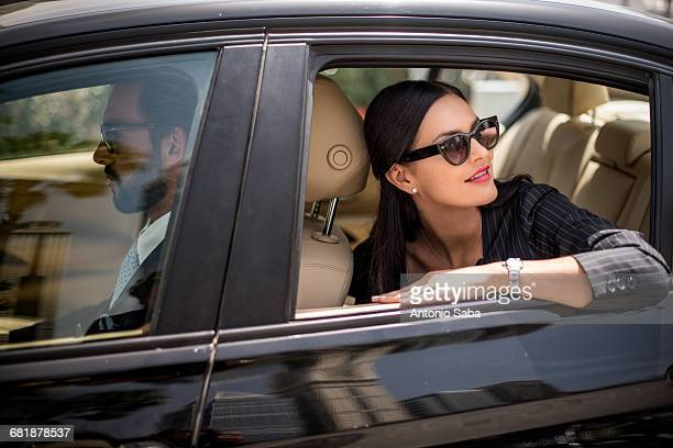stylish businesswoman looking back from backseat car window, dubai, united arab emirates - wealth stock pictures, royalty-free photos & images