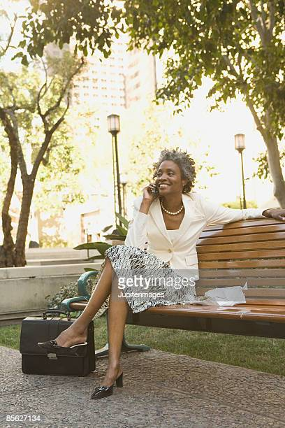 Stylish businesswoman on cell phone on park bench