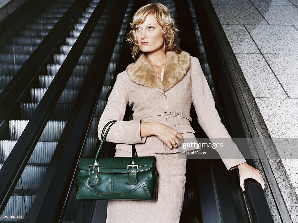 Stylish Businesswoman Wearing a Pink Tweed Suit Standing on an Elevator : Stock Photo