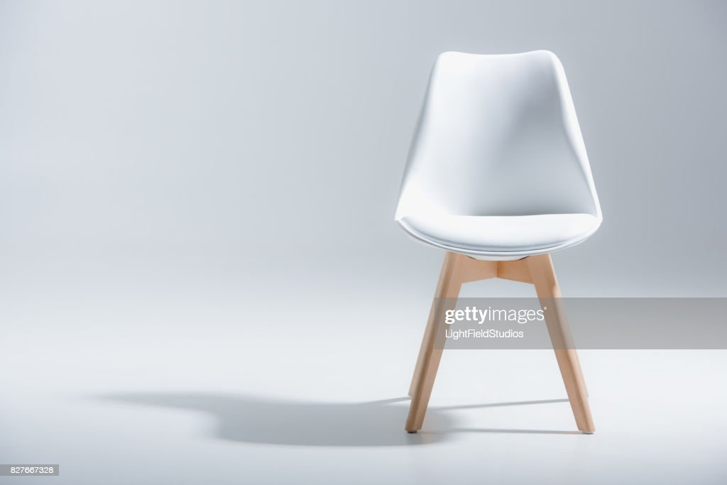 stylish chair with white top and light wooden legs standing on white : Stock Photo