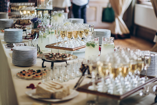 stylish champagne glasses and food  appetizers on table at wedding reception. luxury catering at celebrations. serving food and drinks at events concept 961798406