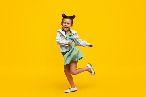Stylish child smiling and dancing 1152823482