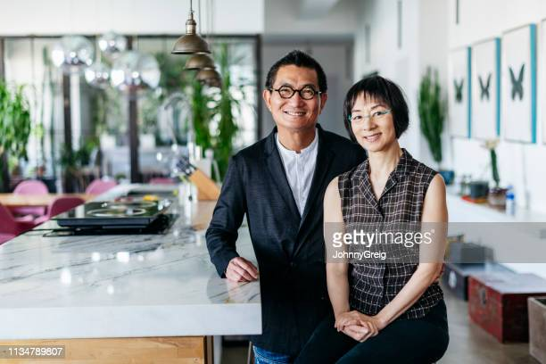 stylish chinese couple in modern office smiling towards camera - chinese ethnicity stock pictures, royalty-free photos & images