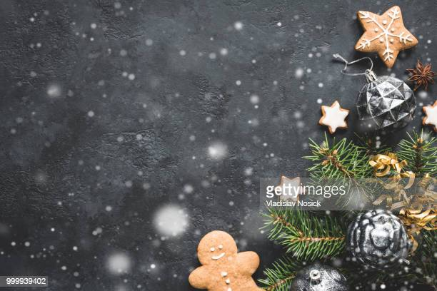 Stylish Christmas background with falling snow, vintage toys, fir tree and cookies on black stone