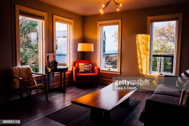 stylish clean neat living room at sunset - bruin stockfoto's en -beelden