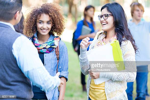 Stylish college students talking together outdoors on campus