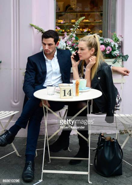 Stylish couple stop for a snack at a coffee and dessert shop in the Belgravia district of London, England.
