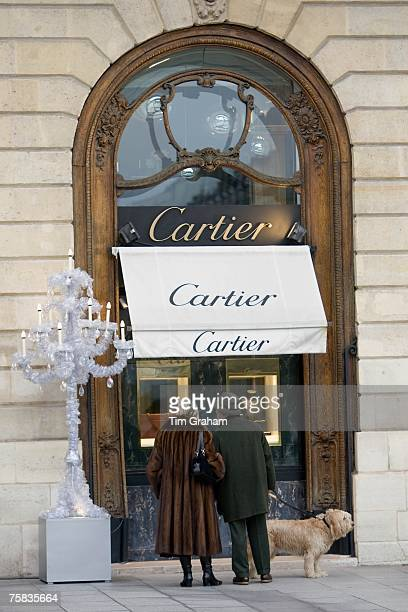 Stylish couple with dog look in Cartier shop window in Place Vendome Central Paris France