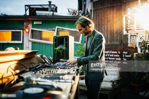 Stylish DJ Performing Using Turntables At Open Air Nightclub