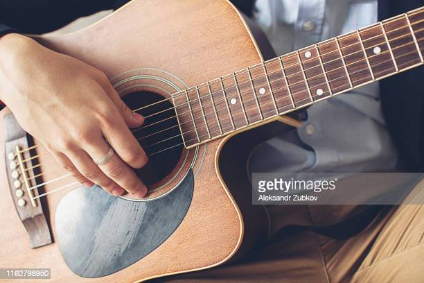 stylish, fashionable man in a blue shirt, dark blue jacket and brown pants playing guitar. the concepts of hobby, passion and interest in music. hands guy touch the strings of the guitar, close-up. - hands in her pants stock pictures, royalty-free photos & images