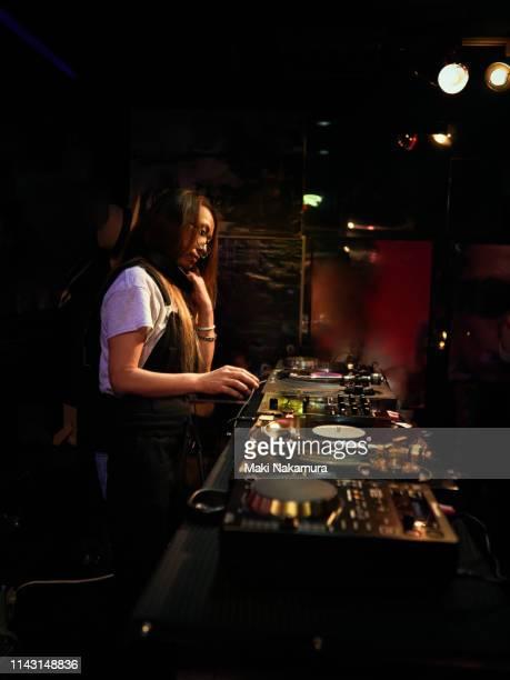 stylish female dj playing using turntable in nightclub - chigasaki stockfoto's en -beelden