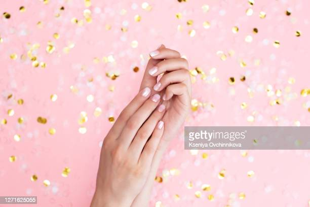 stylish female pink and white manicure. beautiful young woman's hands on pink pastel background with festive multicolored confetti. trendy geometric pattern. art manicure. - oval kennington stock pictures, royalty-free photos & images