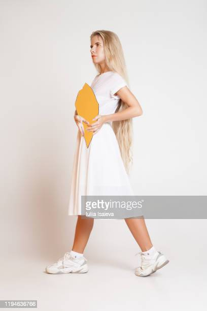 stylish female with yellow shard - woman in broken shoe heel stock pictures, royalty-free photos & images