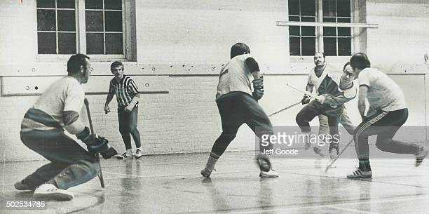Stylish form is exhibited by Dave Todd of Jets as he unleashes shot at goalie Ken Kouch of Kings in Broadview YMCA floor hockey league game Referee...