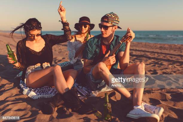 Stylish friends playing guitar on the beach, sunset