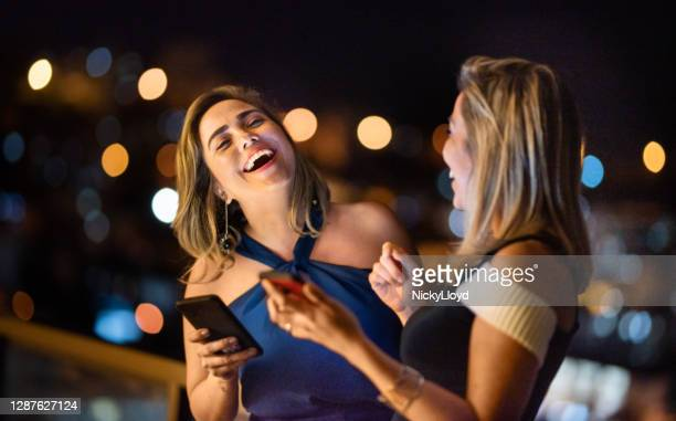 stylish friends standing on a balcony at night and laughing at a message - evening gown stock pictures, royalty-free photos & images
