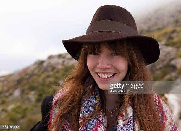 stylish girl with hat smiling in nature