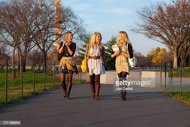 stylish girls walking and talking - rok stockfoto's en -beelden