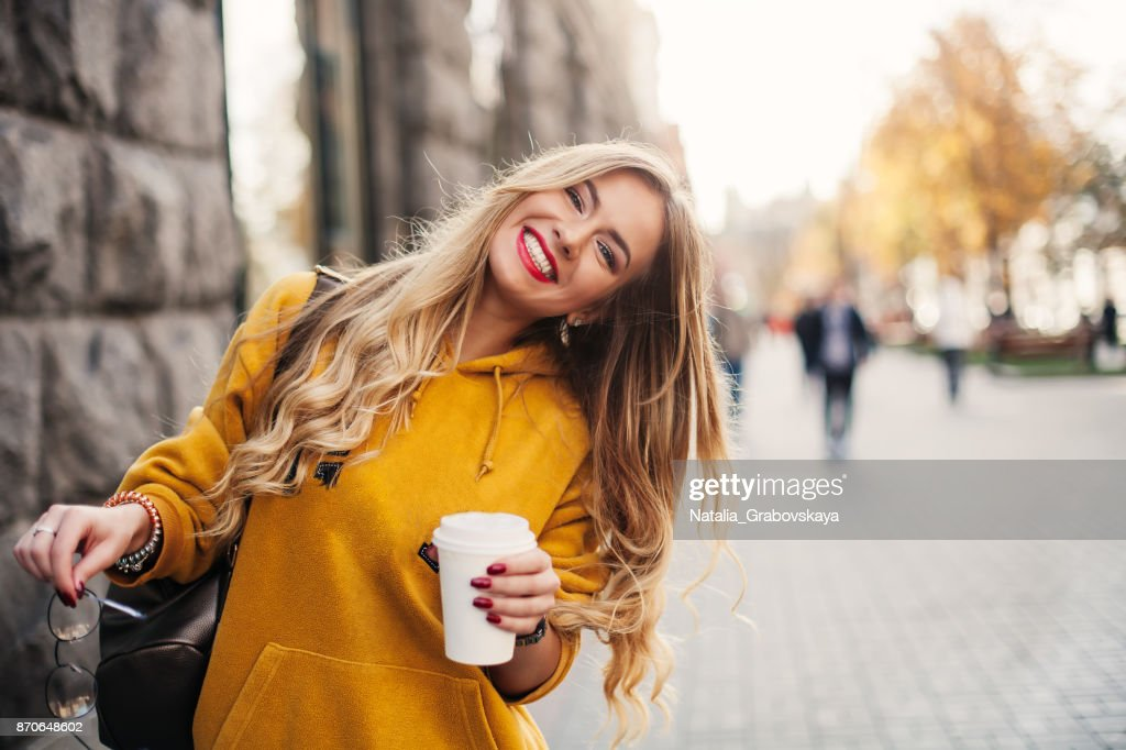 Stylish happy young woman wearing boyfrend jeans, white sneakers bright yellow sweetshot.She holds coffee to go. portrait of smiling girl in sunglasses and with bag : Stock Photo