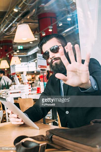 Stylish Hipster in a book-cafe protect his privacy