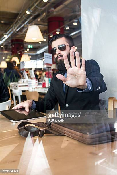 stylish hipster in a book-cafe protect his privacy - pjphoto69 stock pictures, royalty-free photos & images