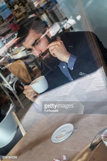 Stilvolle Hipster in einem Buch-Café mit Kaffee oder cappuccino