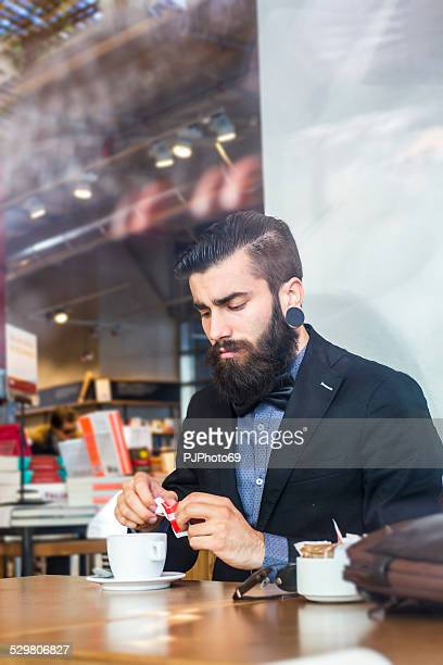 stylish hipster in a book-cafe with coffee or cappuccino - pjphoto69 stock pictures, royalty-free photos & images