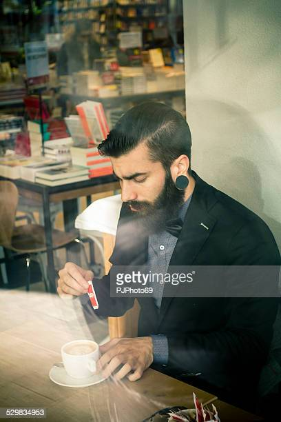 Stylish Hipster in a book-cafe with coffee or cappuccino
