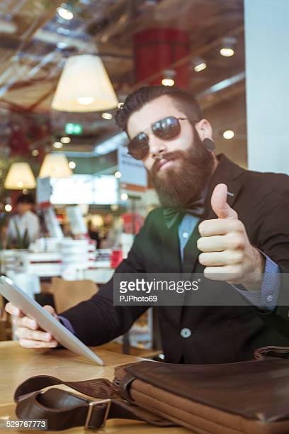 Stylish Hipster in a book-cafe with thumb up