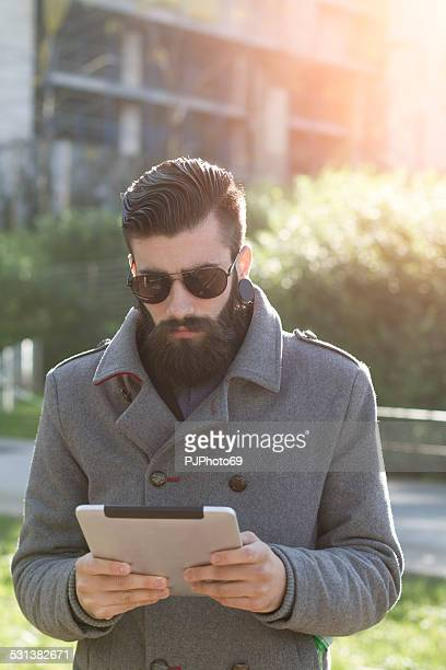 Stylish Hipster outdoor with digital tablet