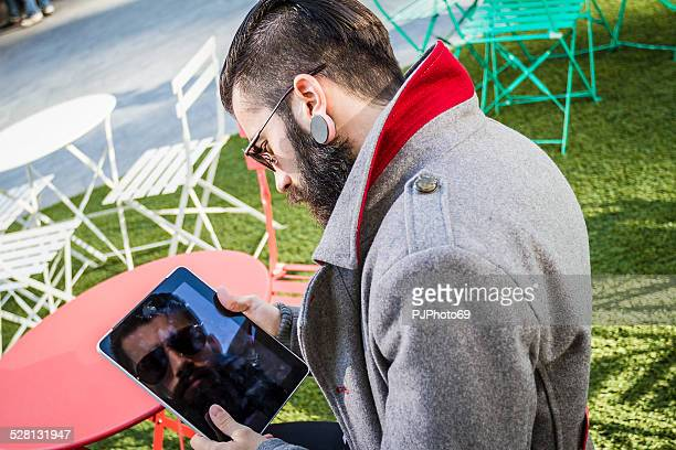 stylish hipster sitting outdoor with digital tablet - pjphoto69 stock pictures, royalty-free photos & images