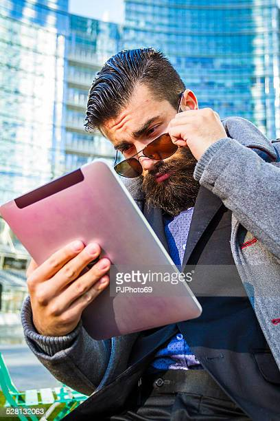 Stylish Hipster sitting outdoor with digital tablet