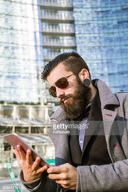 stilvolle hipster mit digitalen tablet sitzen im freien - pjphoto69 stock-fotos und bilder