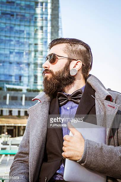 stylish hipster sitting outdoor with digital tablet - pjphoto69 stockfoto's en -beelden