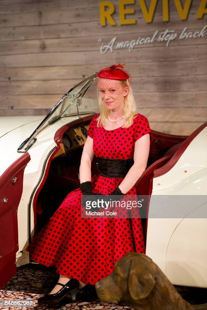 Stylish lady in period dress at 'The Earls Court Motorshow' building poses for photos with a 1950's Jaguar XK 120 at Goodwood on September 8th 2017...