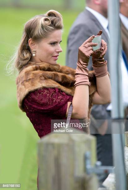 Stylish lady spectator wearing fur stole taking photos trackside at Goodwood on September 8th 2017 in Chichester England