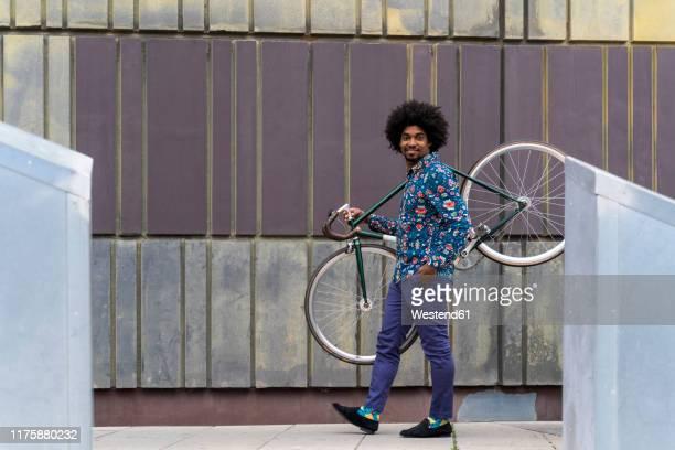 stylish man carrying bicycle in the city - buntes hemd stock-fotos und bilder