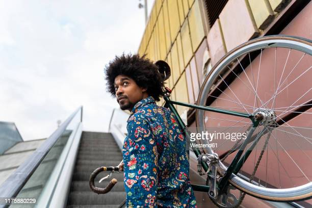 stylish man carrying bicycle on escalator - cool attitude stock pictures, royalty-free photos & images