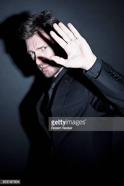 Stylish man in black suit shielding eyes