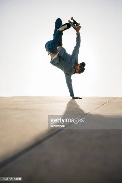 stylish man in denim outfit showing trick with skate in handstand - handstand stock pictures, royalty-free photos & images