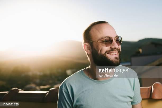 テラスで晴れた午後にスタイリッシュな男 - カラーサングラス ストックフォトと画像