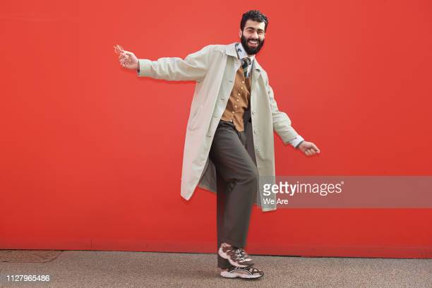 Stylish man posing for camera in playful moment.
