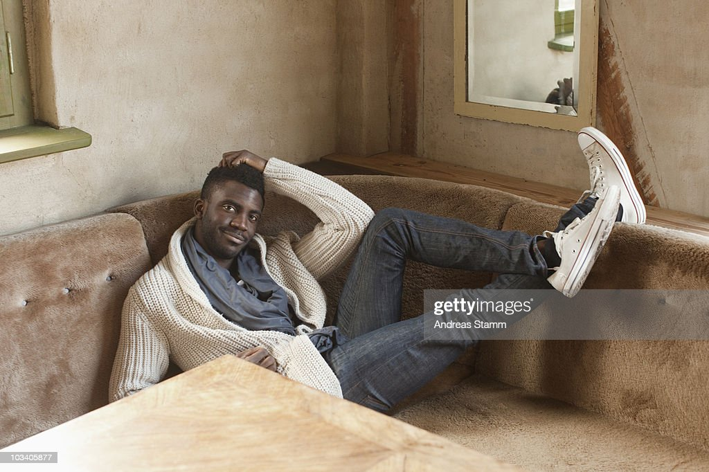 A stylish man reclining in a booth : Stock Photo