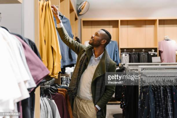 stylish man shopping in a clothes store - man shopping stock pictures, royalty-free photos & images