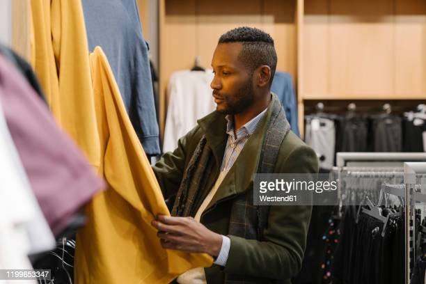 stylish man shopping in a clothes store - men fashion stock pictures, royalty-free photos & images