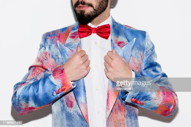 stylish man wearing a colorful suit and a red bow tie - multi colored suit stock pictures, royalty-free photos & images
