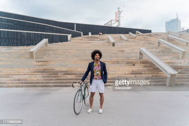 stylish man with bicycle standing at stairs - men fashion stock pictures, royalty-free photos & images