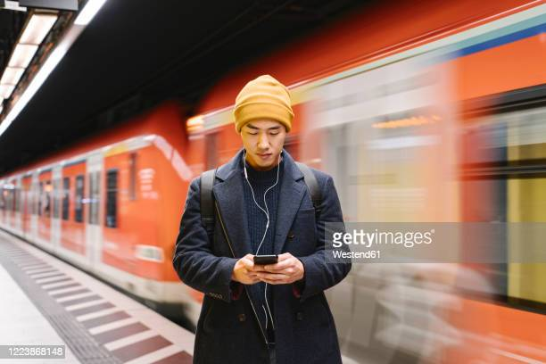 stylish man with smartphone and earphones in metro station - blurred motion stock pictures, royalty-free photos & images