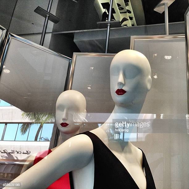 Stylish mannequins in storefront window