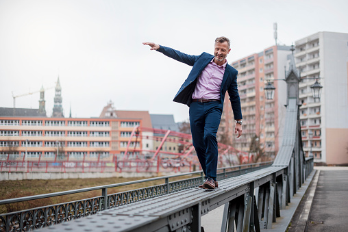 Stylish mature businessman wearing blue suit balancing on railing of bridge - gettyimageskorea
